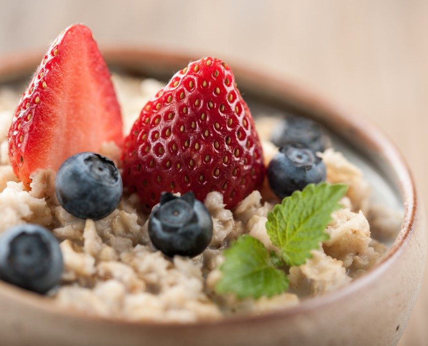 Traditional oatmeal bowl topped with strawberries and blueberries